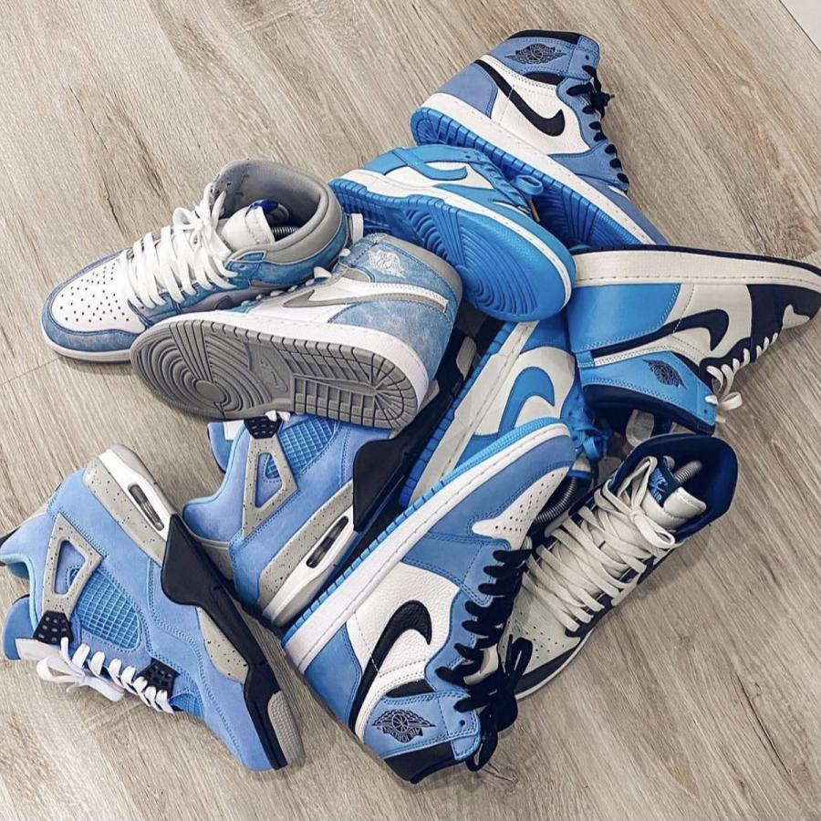 A heap of blue Jordan trainers, shown from above on a wooden floor