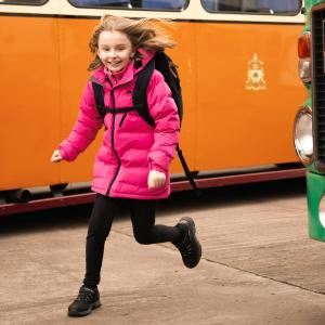 Girl in pink jacket and black backpack is running by a school bus