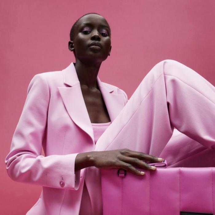 Seated model in head-to-toe pink tailoring with matching clutch from Ted Baker